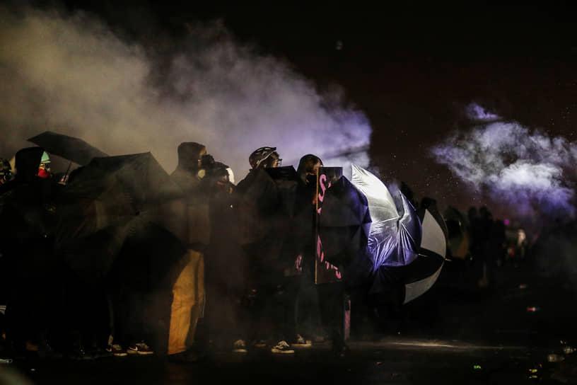 Бруклин-Сентер, США. Протестующие прикрываются зонтами от дыма