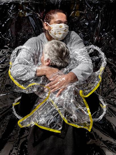 Фотография года — снимок датчанина Мадса Ниссена под названием «Первое объятие», сделанный в августе 2020 года. На нем изображена 85-летняя жительница дома престарелых в Сан-Паулу, которую обнимает медсестра