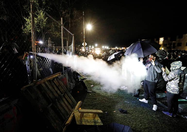 Бруклин-Сентер, Миннесота, США. Полиция применяет перцовый спрей во время беспорядков, спровоцированных убийством афроамериканца Данте Райта