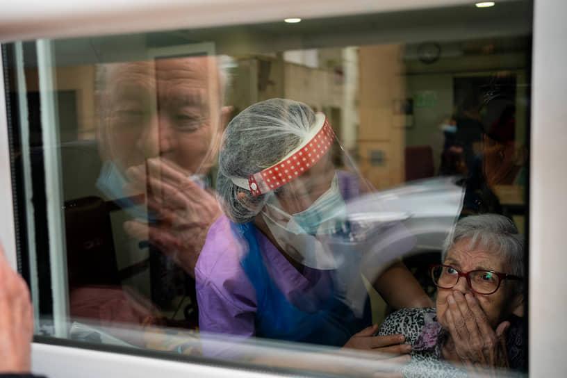 Барселона, Испания. Пожилой мужчина шлет воздушный поцелуй женщине в доме престарелых
