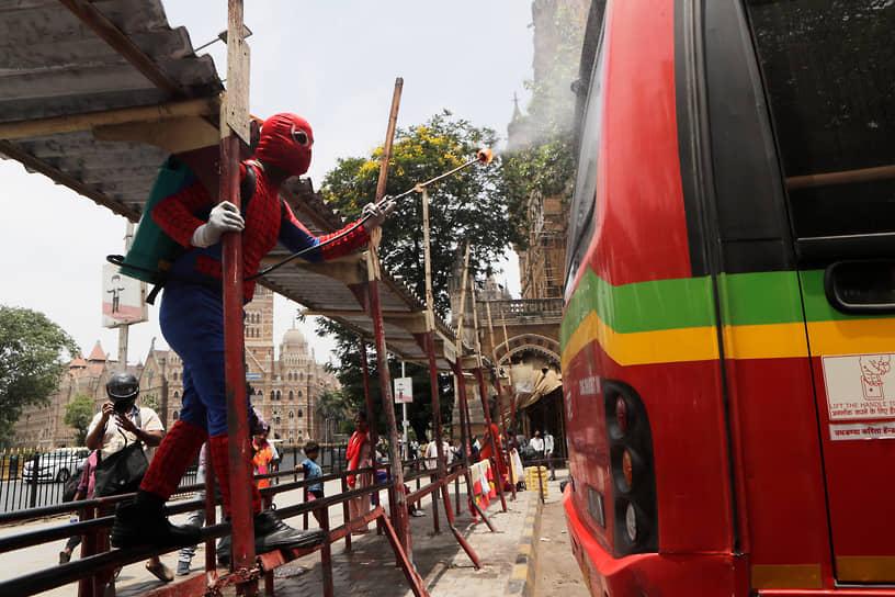 Мумбаи, Индия. Мужчина в костюме Человека-паука дезинфицирует автобус