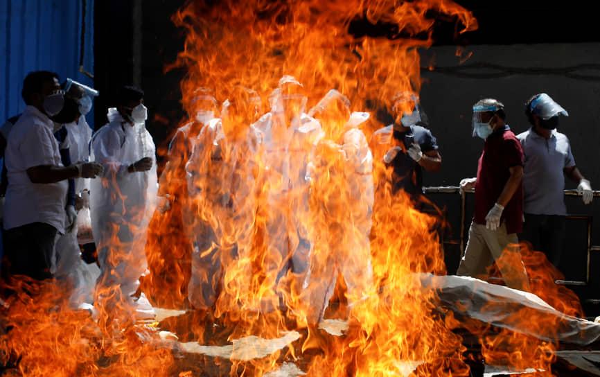 Нью-Дели, Индия. Люди в средствах индивидуальной защиты в крематории