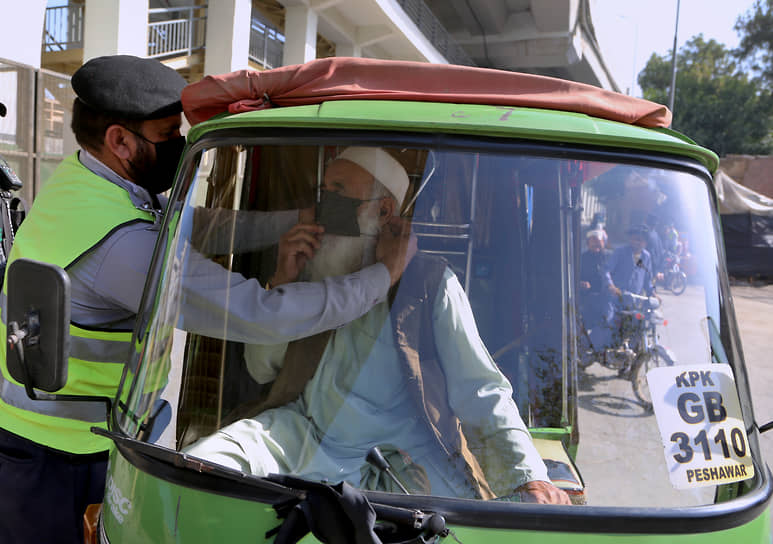 Пешавар, Пакистан. Полицейский объясняет водителю рикши, как носить медицинскую маску