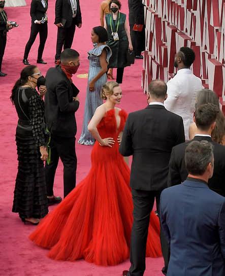 Актриса и режиссер Реджина Кинг (в голубом платье на заднем плане) и актриса Аманда Сайфред (в красном платье) на красной дорожке