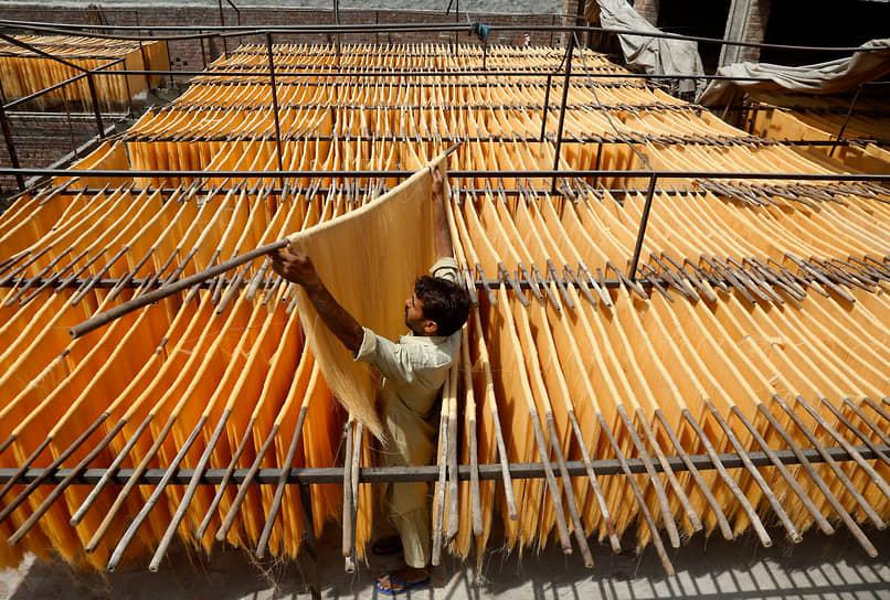 Лахор, Пакистан. Мужчина раскладывает лапшу