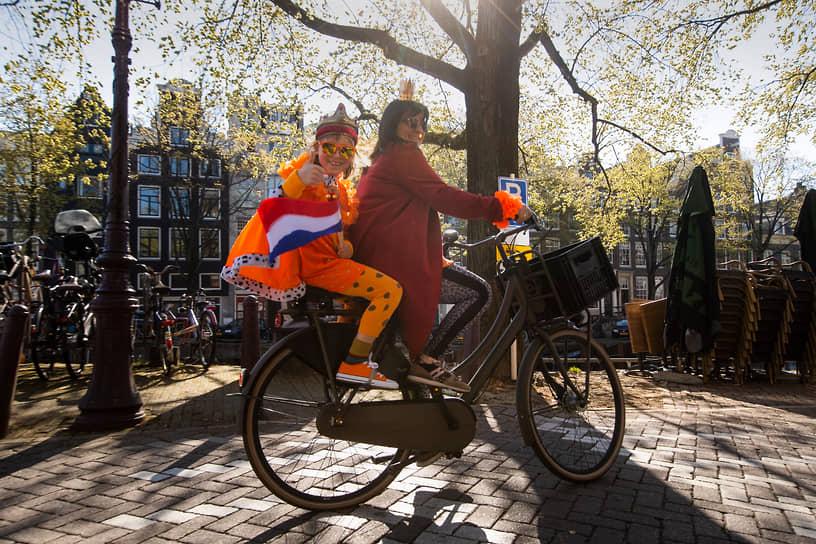 Амстердам, Нидерланды. Мать с дочерью отмечают день рождения короля страны Виллема-Александра