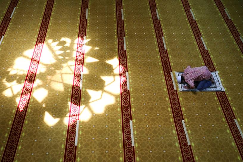Шах-Алам, Малайзия. Мужчина молится в мечети