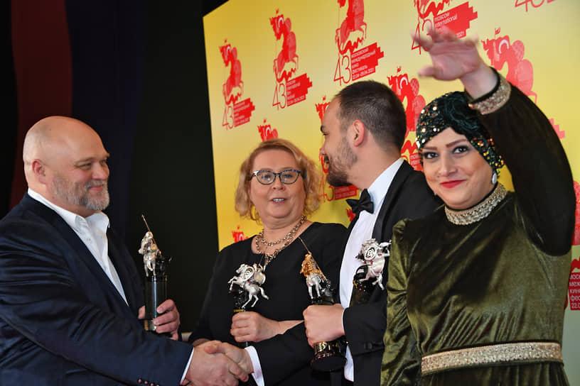 Слева направо: режиссер Алексей Федорченко, продюсер Юлия Мишкинене и режиссер Андрей Хуцуляк во время церемонии