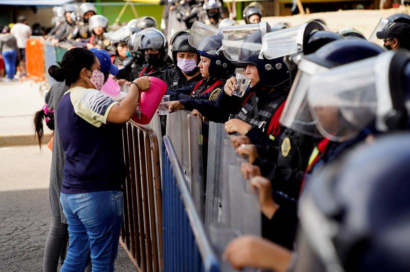 Мехико, Мексика. Женщина делится водой с полицейскими в оцеплении у места крушения метромоста