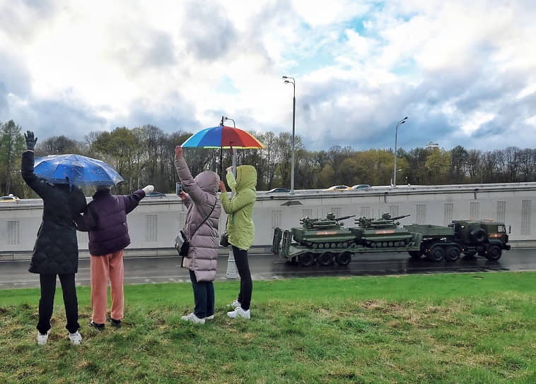 Зрители смотрят проход военной техники по городу