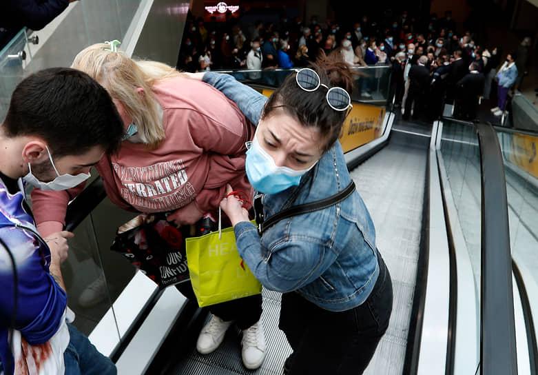 Белград, Сербия. Женщине помогают подняться по эскалатору