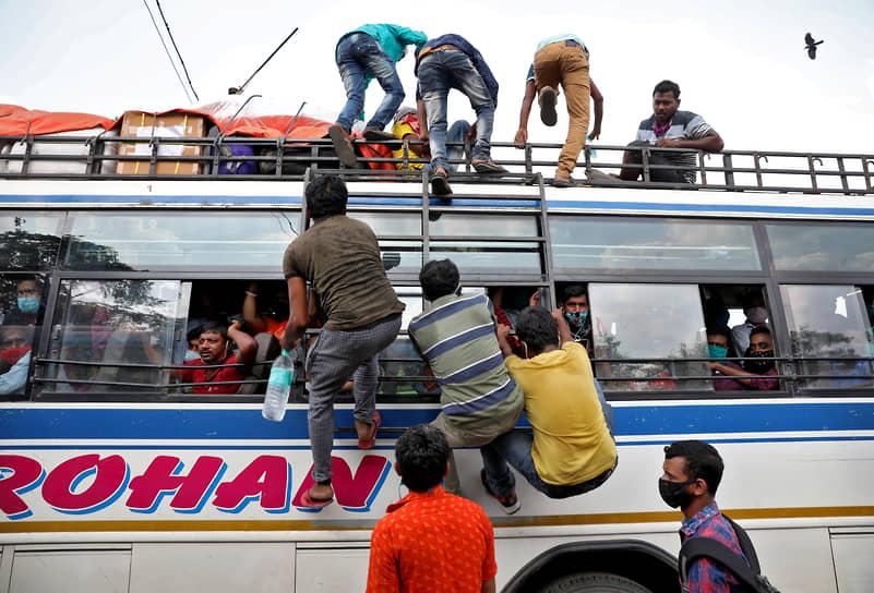 Калькутта, Индия. Рабочие залезают в переполненный автобус