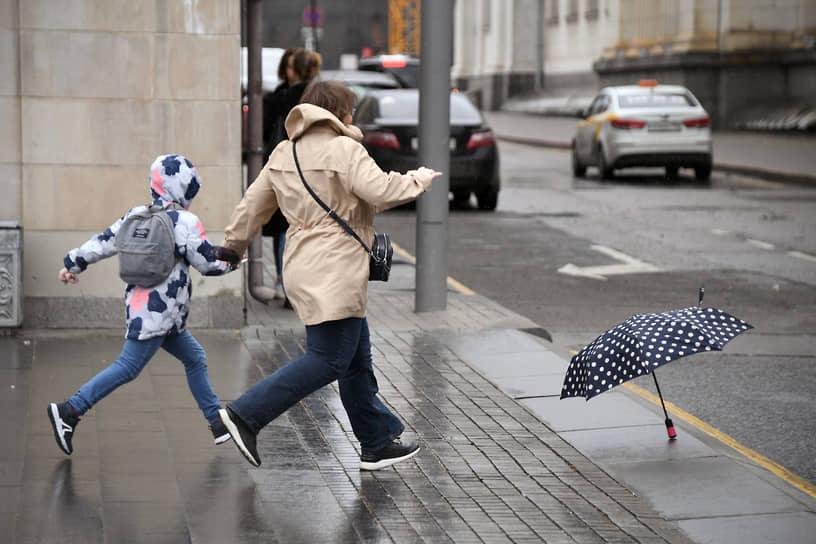 Москва, Россия. Женщина бежит с ребенком за улетевшим зонтом