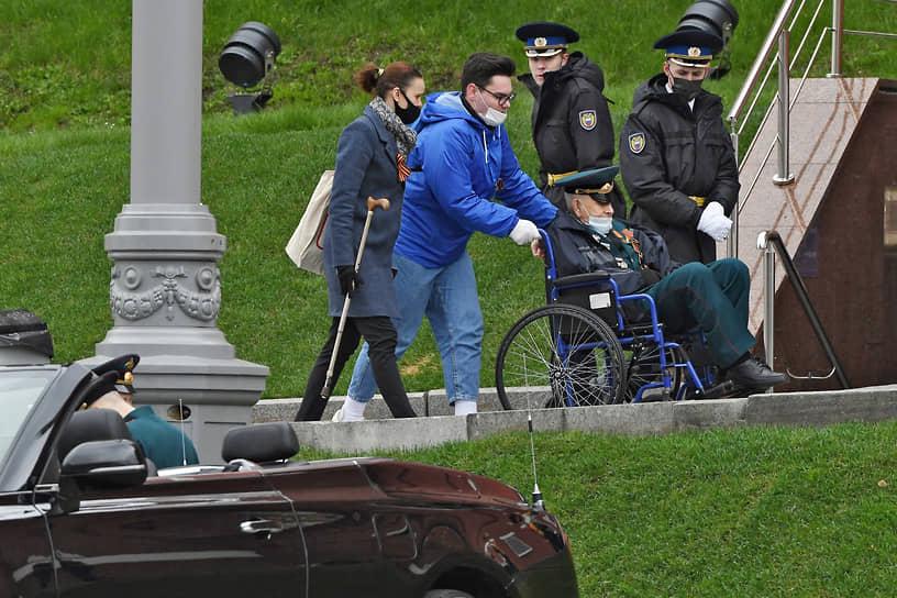 Москва. Волонтеры помогают ветеранам занять свои места на зрительской трибуне перед началом военного парада на Красной площади