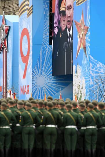 Москва. Президент России Владимир Путин (на экране) во время парада