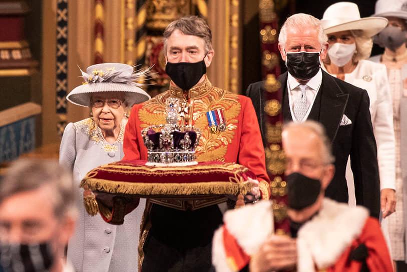 Лондон, Великобритания. Королева Елизавета II с принцем Чарльзом (на фото справа) перед выступлением на сессии парламента