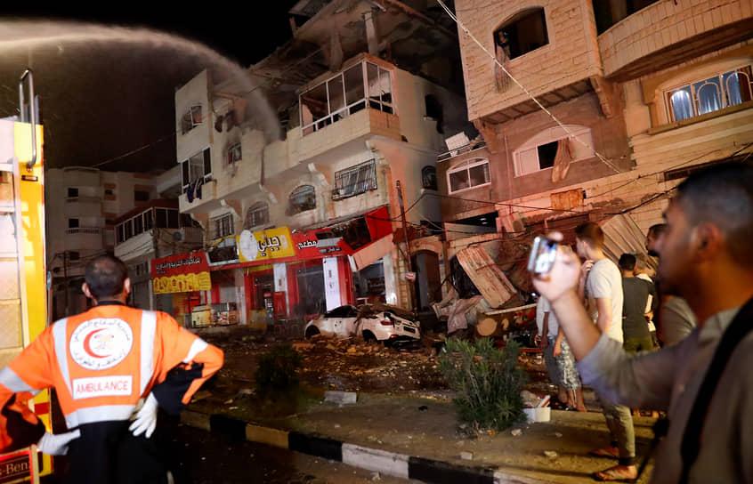 Пожарные тушат здание в секторе Газа, загоревшееся в результате бомбардировки