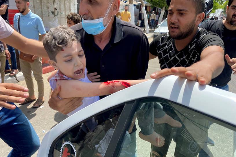 Палестинского ребенка везут в госпиталь после ранения при израильском авиаударе в секторе Газа