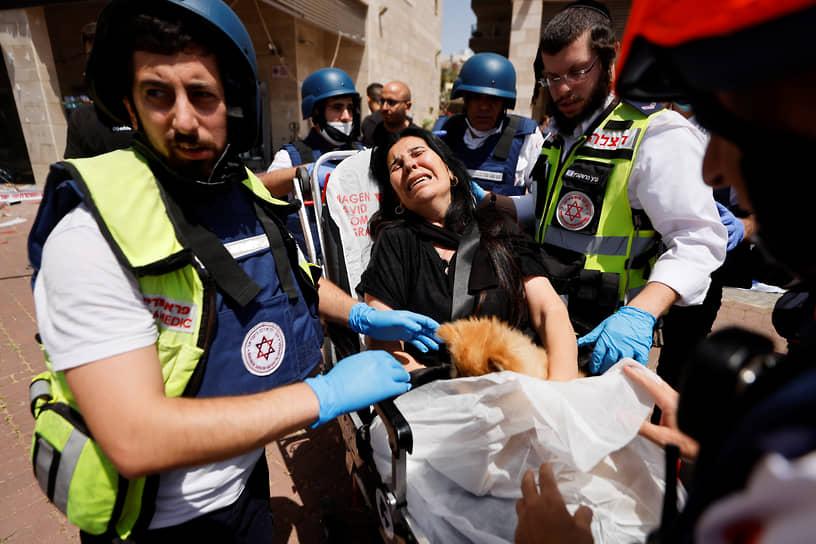 Медики эвакуируют женщину с места авиаудара «Хамаса» по израильскому Ашкелону