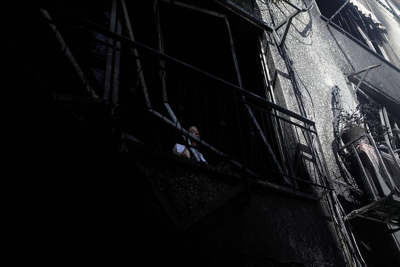 Петах-Тиква, Израиль. Женщина смотрит из окна поврежденного в результате обстрела дома