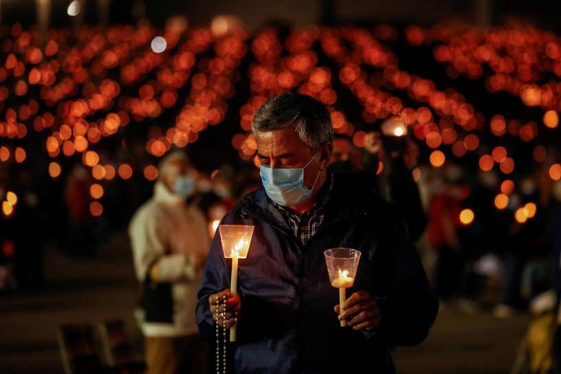Фатима, Португалия. Паломник держит в руках свечи
