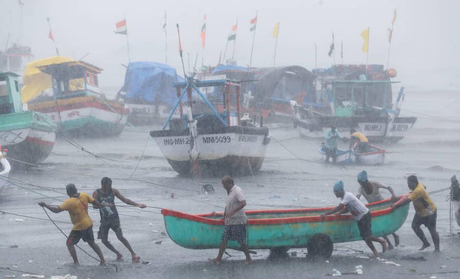 Мумбаи, Индия. Рыбаки перетаскивают лодку во время непогоды