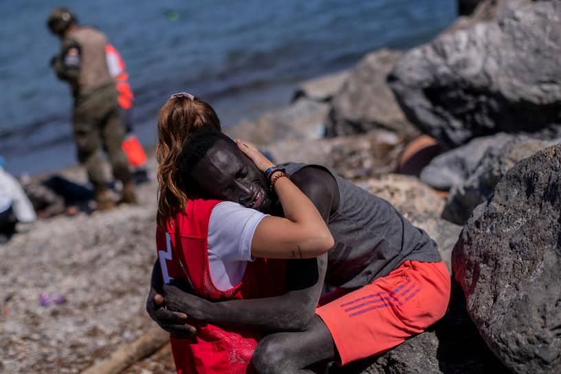 Сеута, Испания. Сотрудница Красного Креста обнимает одного из нелегальных мигрантов, переплывших из Марокко на надувных лодках, кругах, плотах и плавательных досках