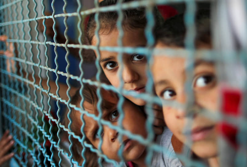 Сектор Газа, Палестина. Дети, покинувшие дома из-за израильских воздушных и артиллерийских ударов, смотрят через окно школы, где они нашли убежище