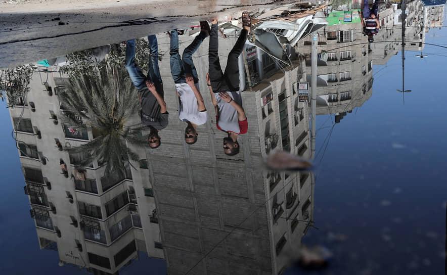 Сектор Газа, Палестина. Молодые люди проходят мимо объектов, по которым был нанесен авиаудар