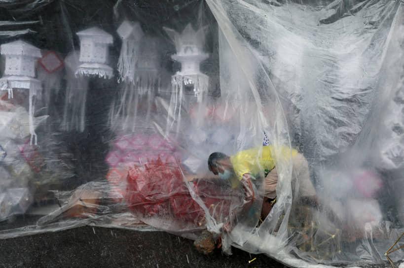Коломбо, Шри-Ланка. Продавец укрывает фонари от дождя