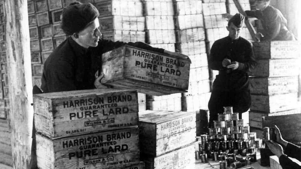 «Не имея сливочного масла, они часто мажут на черный хлеб американское свиное сало. Это, конечно, не роскошь. В условиях суровой русской зимы жиры совершенно необходимы» (на фото — склад с продуктами, прибывшими из США. Ленинградский фронт, 1943 год)