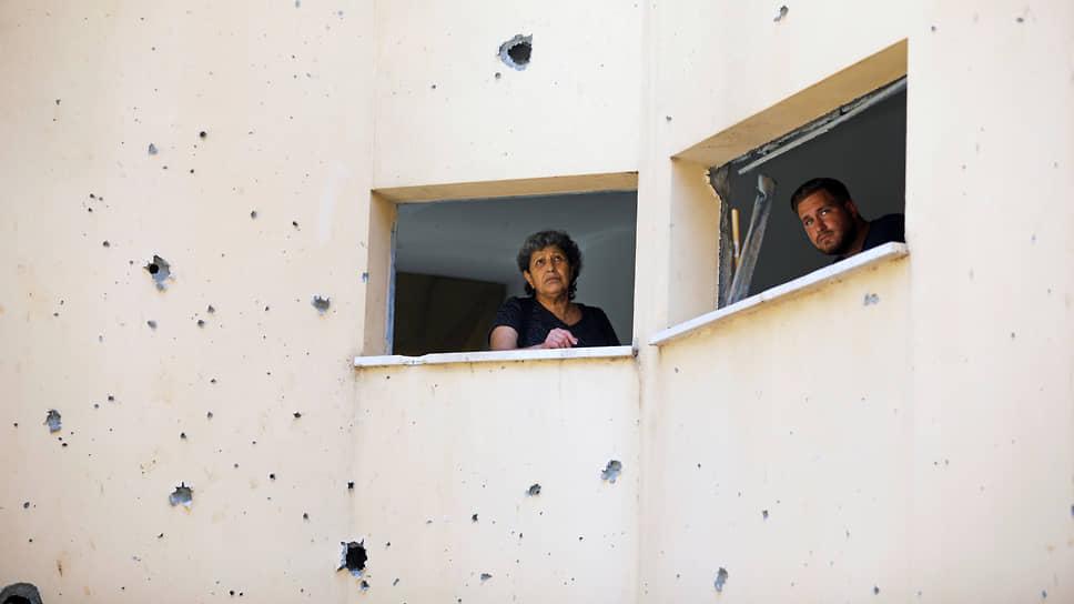 Люди выглядывают из окон здания, поврежденного ударом ракеты из Газы, в Петах-Тиква (Израиль)