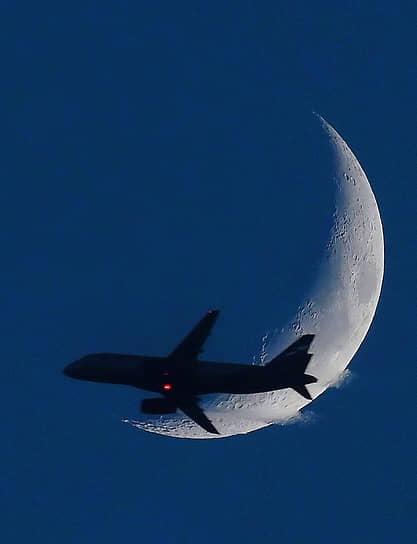 Москва. Самолет в небе на фоне месяца