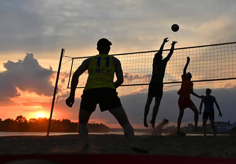 Омск, Россия. Молодые люди играют в волейбол на берегу реки Иртыш