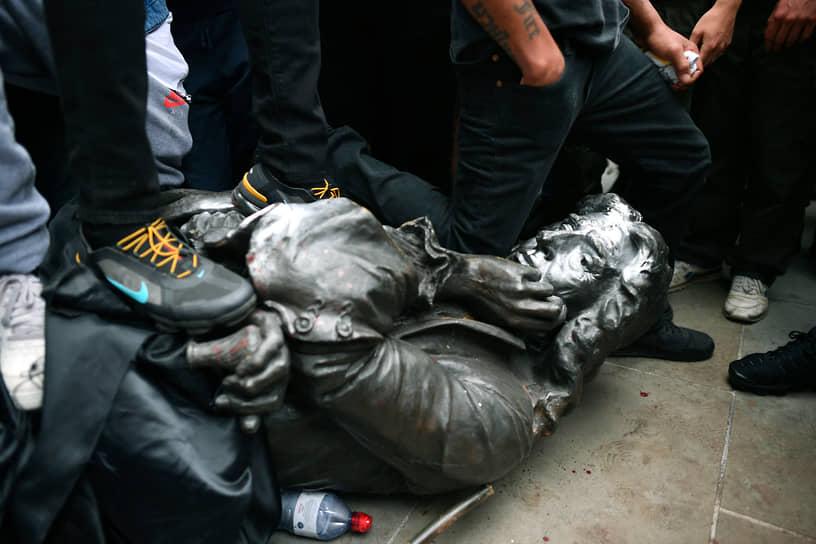 Волна борьбы с монументами также вышла за пределы США. Так, в четырех бельгийских городах демонтировали памятники королю Леопольду II: первую статую, в Антверпене, городские власти убрали с постамента 9 июня, после того как демонстранты облили ее краской и подожгли. В южноафриканском Кейптауне протестующие оторвали голову от бюста британского колонизатора Африки Сесила Родса. После чего сам бюст тоже демонтировали местные власти <br>На фото: снос памятника работорговца Эдварда Кольстона в Великобритании