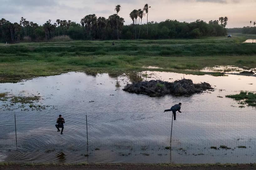 Ла Джойя, штат Техас, США. Мигранты перелезают через забор обратно в Мексику, уходя от американских пограничников