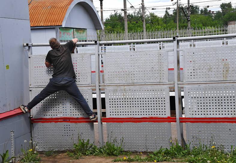 Москва, Россия. Мужчина лезет через ограждение железнодорожной станции