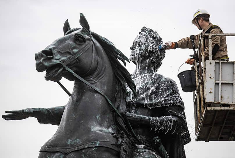 Санкт-Петербург, Россия. Реставратор моет памятник Петру I