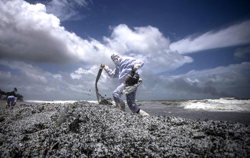 Коломбо, Шри-Ланка. Солдат в защитном костюме на обломках от горящего корабля, выброшенных на берег
