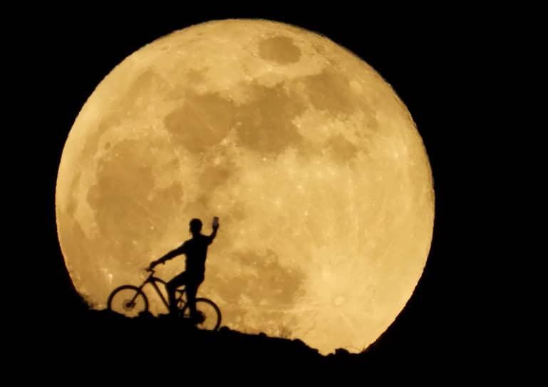 Аргинегин, Испания. Велосипедист фотографирует Луну на Канарских островах