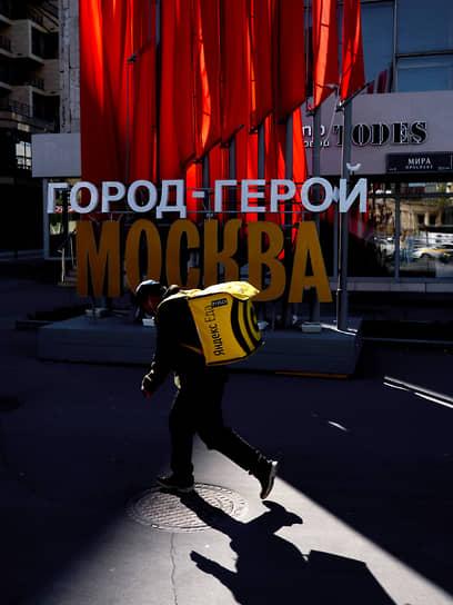 10 мая. Москва. Курьер службы доставки на улице, украшенной ко Дню Победы