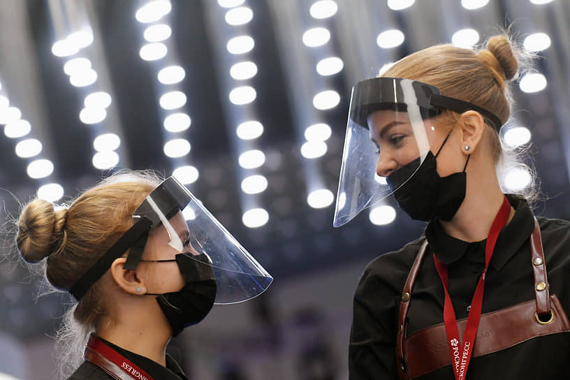 Девушки в защитных медицинских экранах во время работы форума