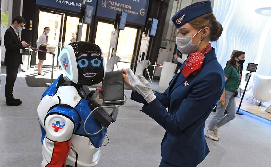 Стюардесса авиакомпании «Россия» рядом с роботом в здании выставочного центра «Экспофорум»