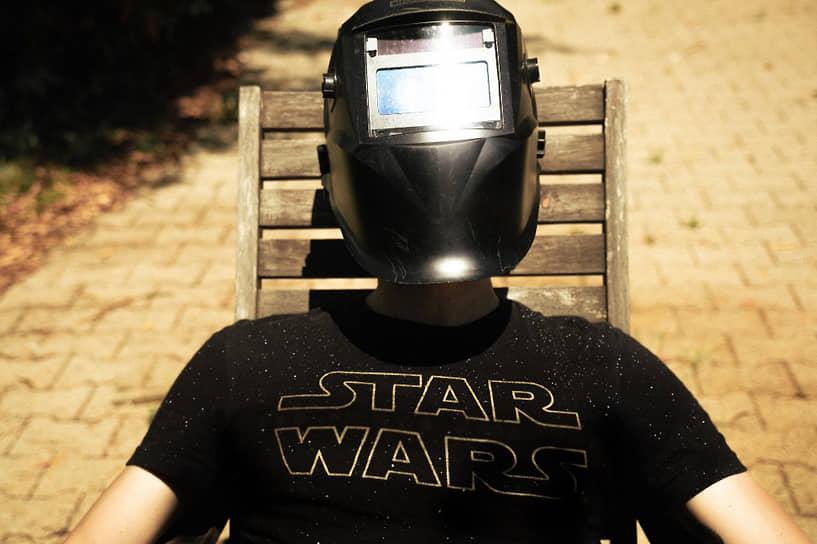 Житель французского Гренобля наблюдает затмение в маске
