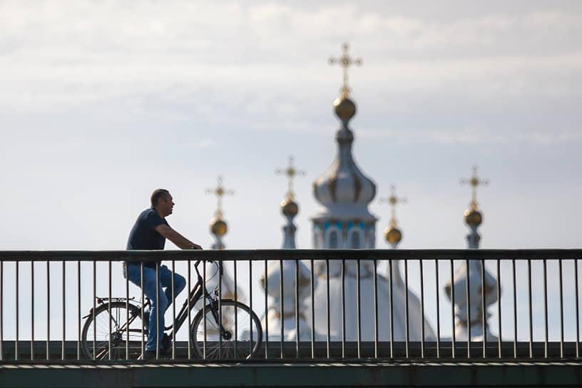 Санкт-Петербург. Мужчина на велосипеде на фоне куполов Смольного собора