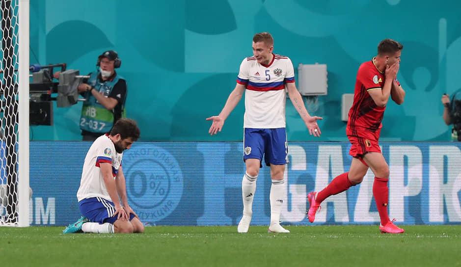 Российские футболисты Андрей Семенов (в центре) и Георгий Джикия (слева) после первого пропущенного гола, который забил бельгиец Ромелу Лукаку