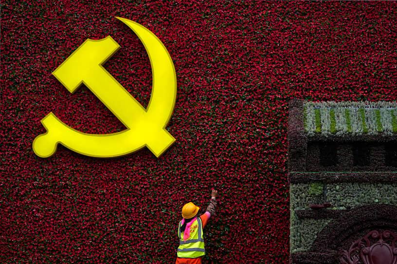 Пекин. Герб Коммунистической партии Китая среди цветов