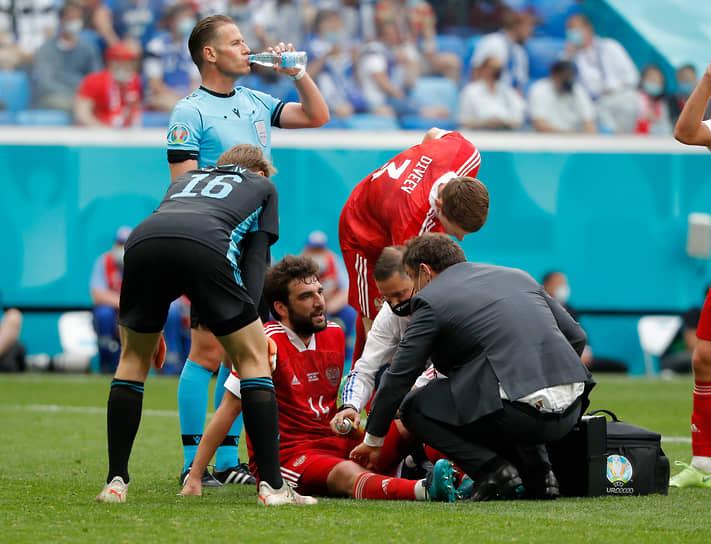 Защитник сборной РФ Георгий Джикия получает медицинскую помощь после травмы