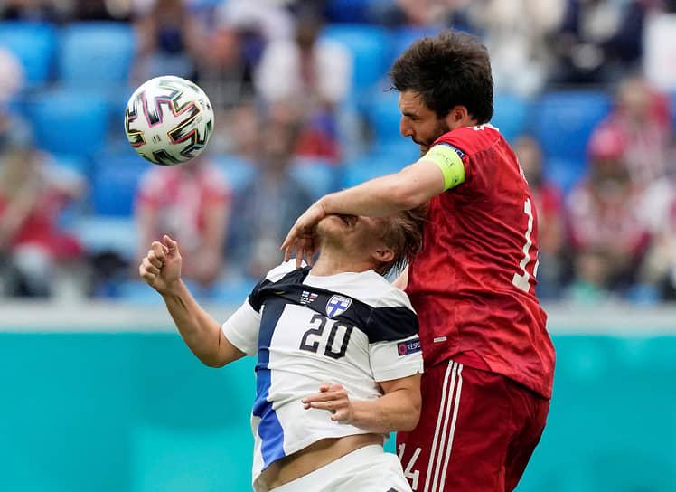Нападающий сборной Финляндии Йоэль Похьянпало и защитник сборной России Георгий Джикия в борьбе за мяч