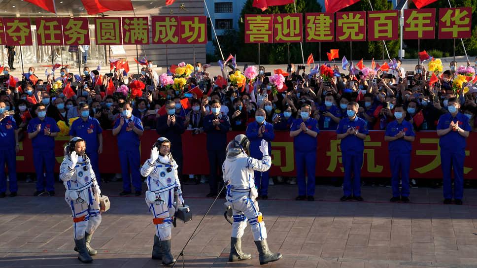 Тан Хунбо, Лю Бомин и Не Хайшэн (слева направо) машут собравшимся перед тем, как сесть в космический корабль